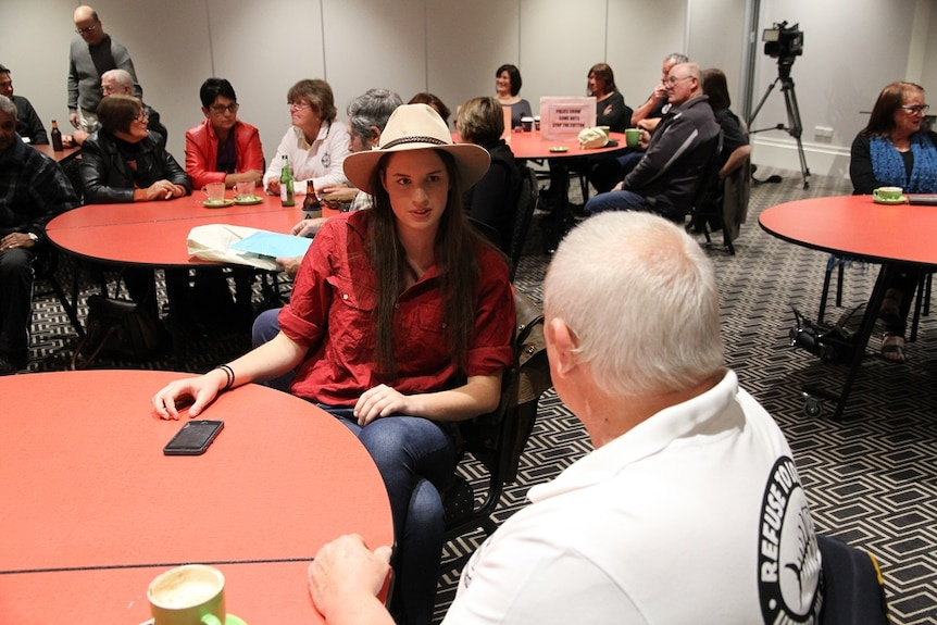a young female wearing a cowboy hat and a serious expression sits facing an older man.