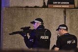 An armed police officer looks through his weapon on London Bridge.