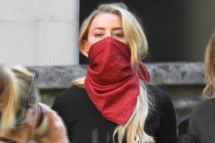 Amber Heard, wearing a red scarf over her mouth for protection, arrives outside London's High Court.