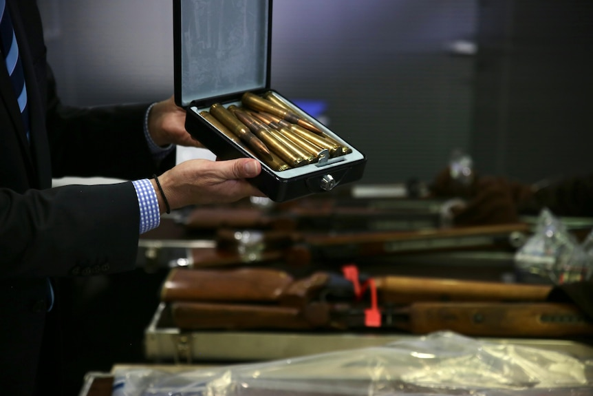 A police detective holds a box of gold coloured ammunition rounds.