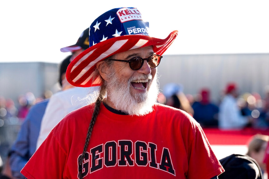You view a man with a ponytail smiling while wearing sunglasses and a bright red shirt that reads 'Georgia'.