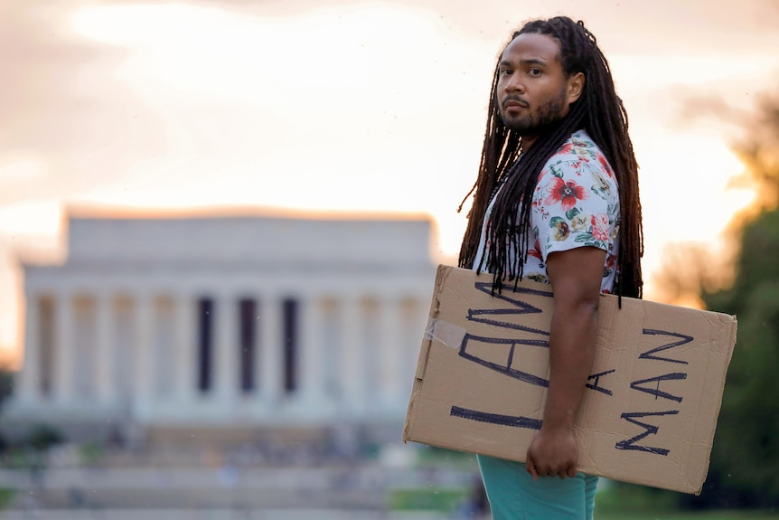 A young Black man with long braids holds a sign reading 'I am a man' near the Lincoln Memorial