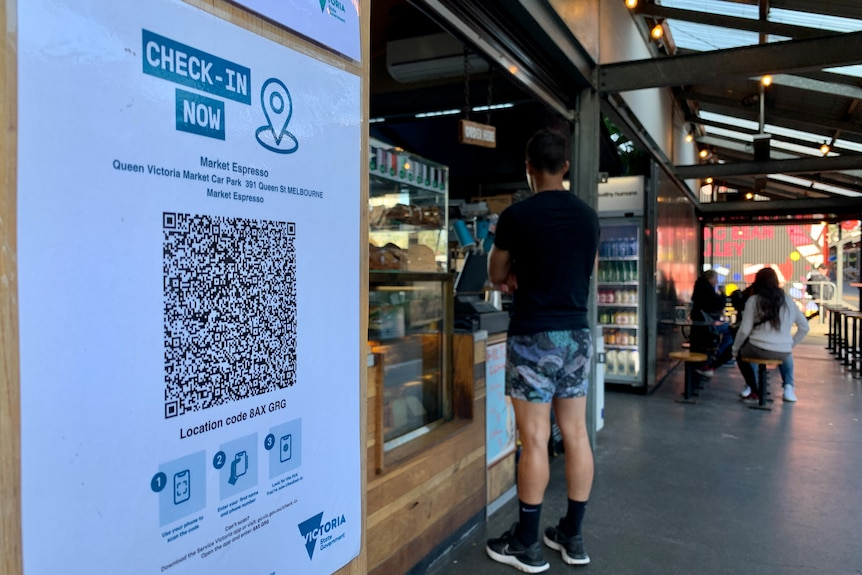 A QR code check in sign at a cafe