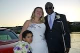 Krystal wears a white wedding dress with purple flowers. Nemoy wears a tuxedo with a purple tie. Jaden stands next to his mother