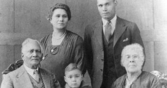 Black and white family portrait of elderly couple with younger man and woman and young boy.