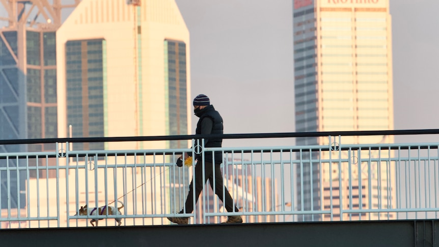 A masked man walks his dog along the footbridge at Claisebrook Cove with the Perth skyline in the background