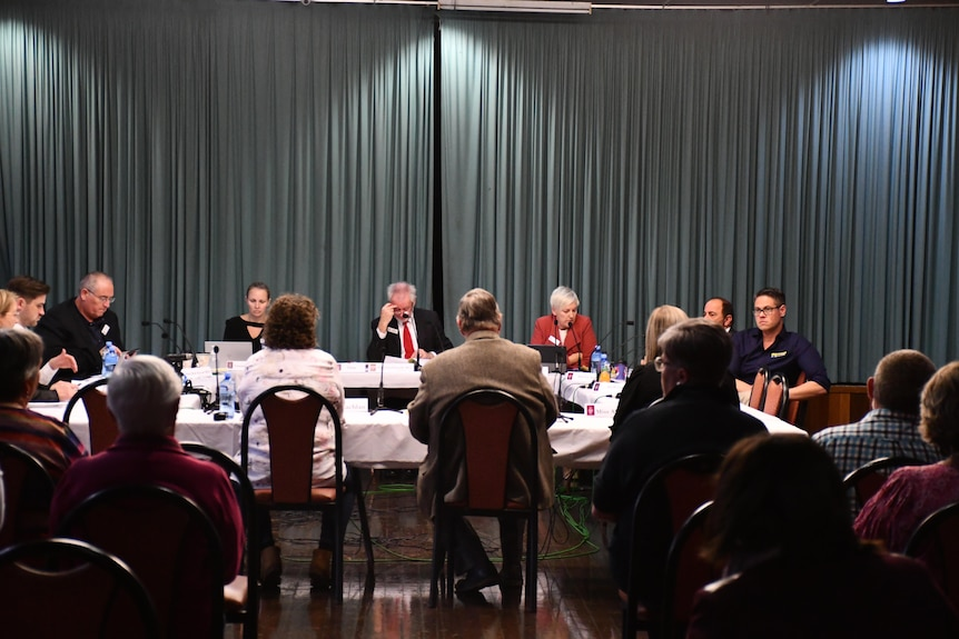 Members of a parliamentary committee sitting at desks, listening to evidence from residents at Cobar