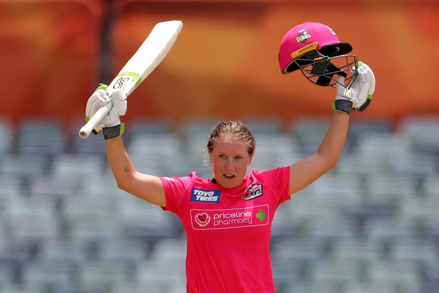 A Sydney Sixers WBBL player holds her bat in one hand and her helmet in the other as she celebrates a century against the Stars.
