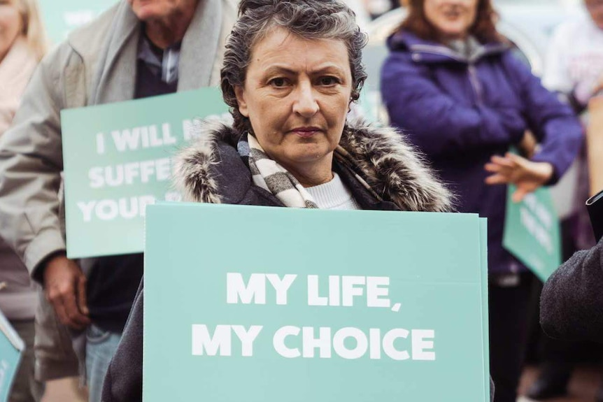 """Voluntary euthanasia supporter holds a """"My Life, My Choice"""" sign."""
