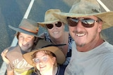 A family of four in akubra hats and sunglasses smile at the camera