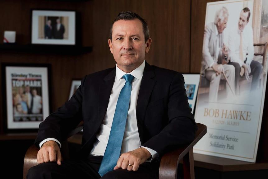 Mark McGowan sitting in an office wearing a suit.