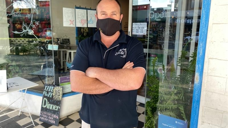 A cafe owner in a mask stands outside his business wearing a black mask