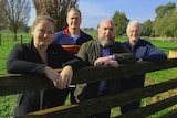 A woman and three men lean against a wooden fence on a rural property.