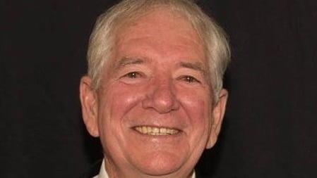 Man wearing dark suit and tie smiling at camera