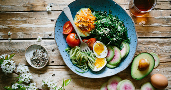 Vegetables, avocado and eggs on a plate.