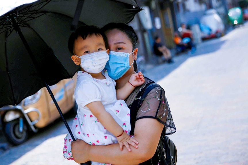 A woman in a blue face masking holding a baby in a floral mask under an umbrella