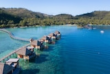 A line of huts sit on stilts in clear blue water with a white beach and mountains covered in trees in the background.