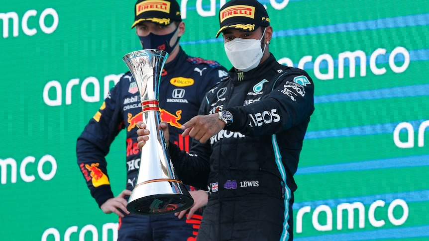 Lewis Hamilton with the trophy ahead of Max Verstappen