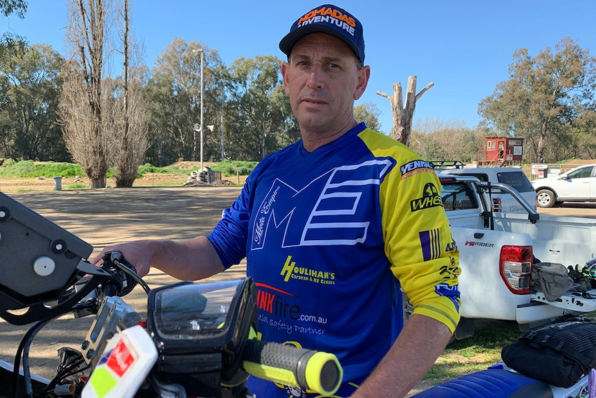 Man looks straight at camera, standing behind a motor bike and wearing racing gear.