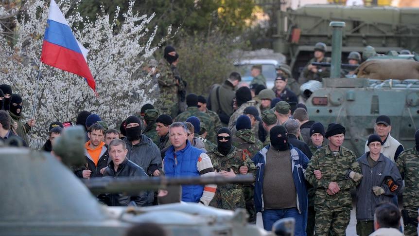 Pro-Russian militiamen cordon off as Russian soldiers storm the Ukrainian military airbase in Belbek