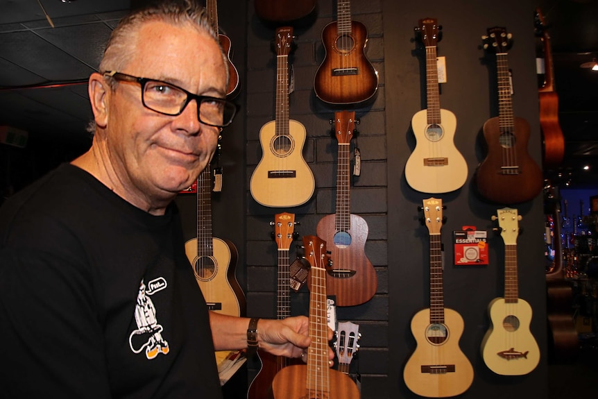 A man next to a range of ukuleles hanging on the wall of a music shop.