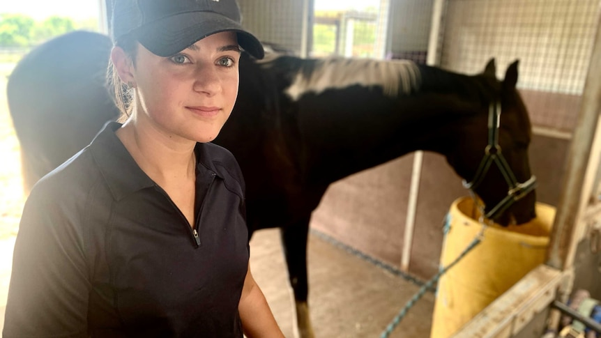 Maddie Nelson stands in a stable wearing a baseball cap, holding her horse, Pablo Cruize, by a rope