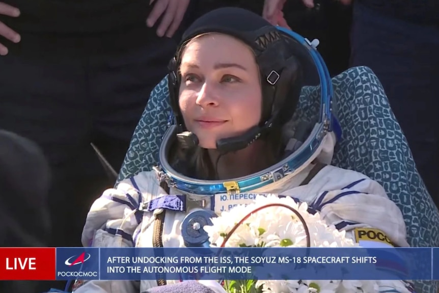 A woman wearing a white space suit and black headphones surrounded by people with bunch flowers in hand