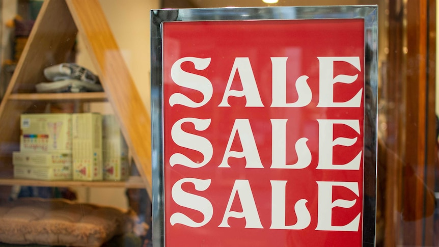 Sign says 'SALE SALE SALE' in a Brisbane shop window with merchandise in the background.