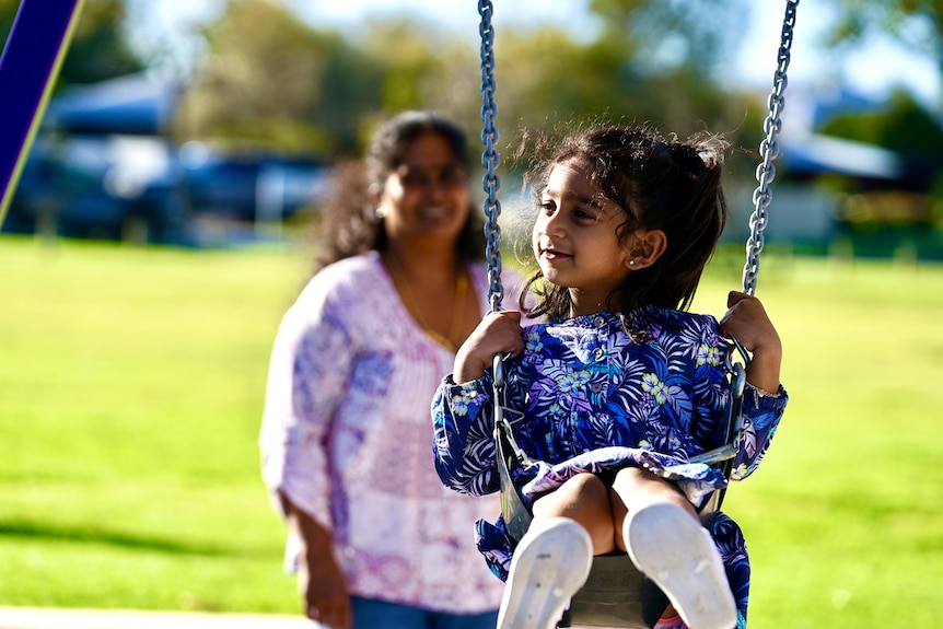 A little girl in a purple floral dress is pushed on a swing with her mother in the foreground slightly out of focus