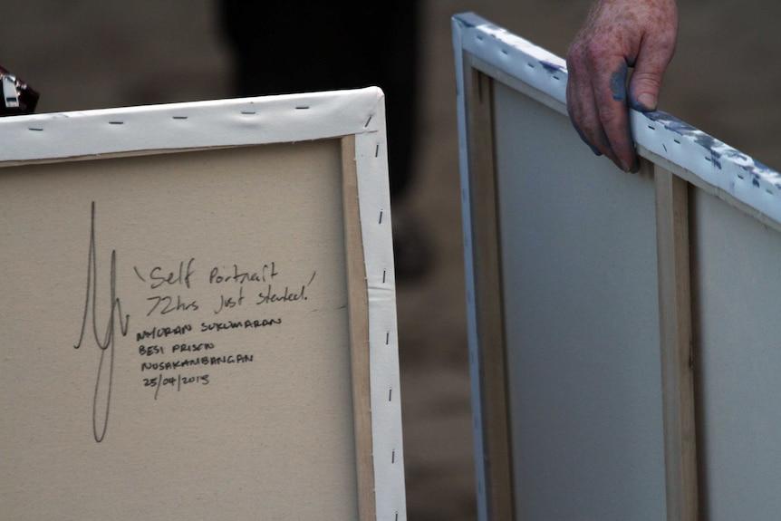 The lawyer of Bali Nine pair, Julian McMahon, carries paintings by death row inmate Myuran Sukumaran