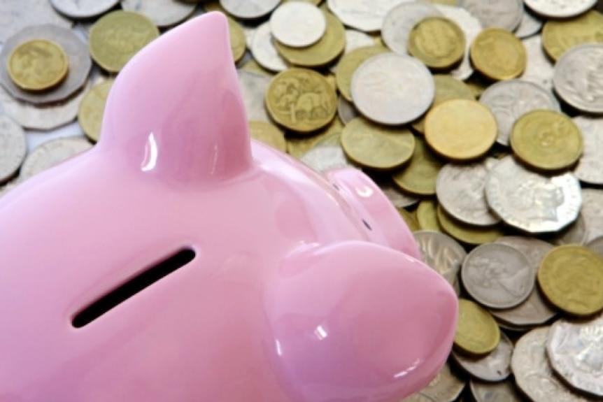 A piggy bank sits on a pile of Australian coins.