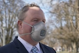 A man in a suit wearing a face mask.
