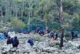 People gathered at mountain tarn.