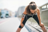 Woman leans over and catches her breath while exercising.