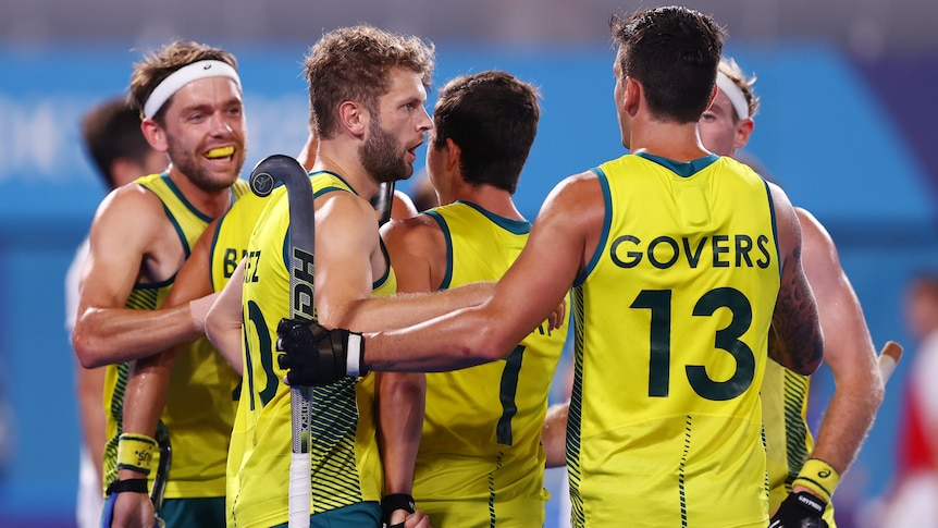 Five Australian men's hockey players embrace each other as they celebrate a goal at the Tokyo Olympics.