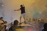 A man stands on a car in the middle of a smoky crowd at night.