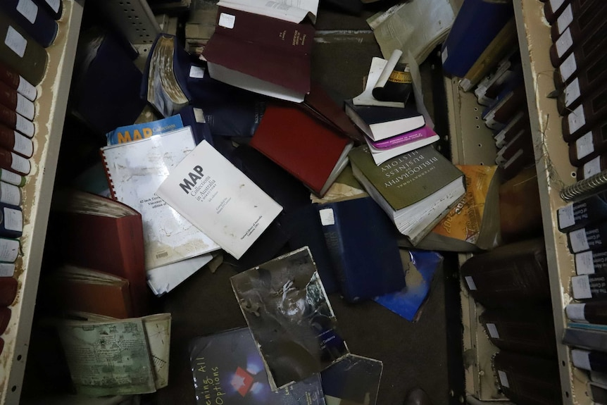 Damaged books on the floor of a library.