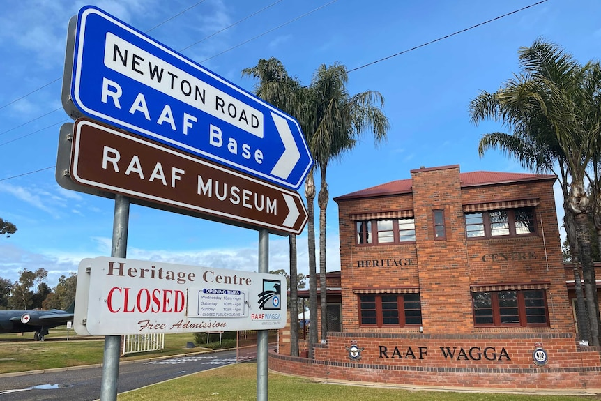 A sign saying RAAF base and RAAF Museum pointing towards a brick building.