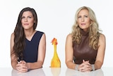 A brunette middle-aged woman and a blonde woman smirk while sitting behind a white desk. In between them is a rubber chicken.
