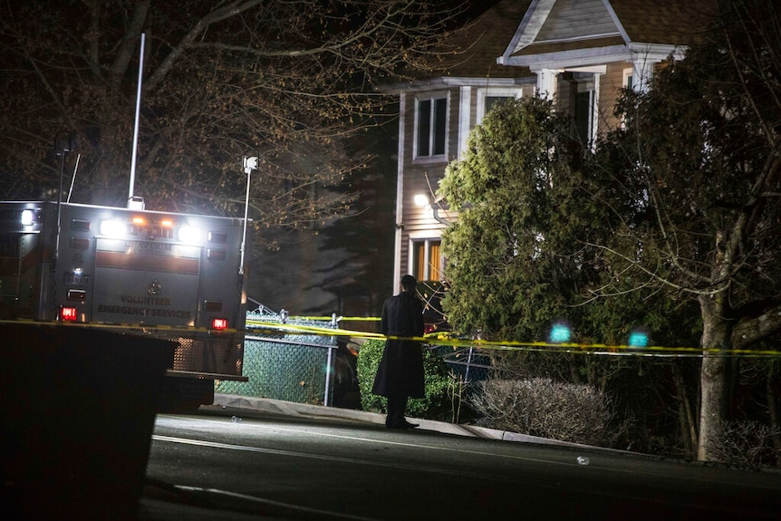 At night, you view a lone Orthodox Jewish man behind police tape between a Jewish ambulance and a house.
