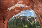 A rock climber crawls upside down along an overhang, with a beautiful vista of mountains in the background.