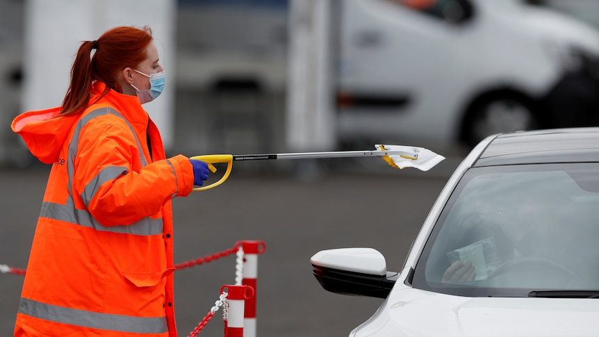 A health worker in orange attire collects a COVID-19 test from a car