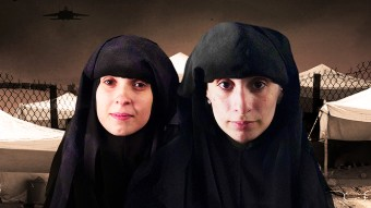 Two women wearing black head-covering garments look directly into the camera.