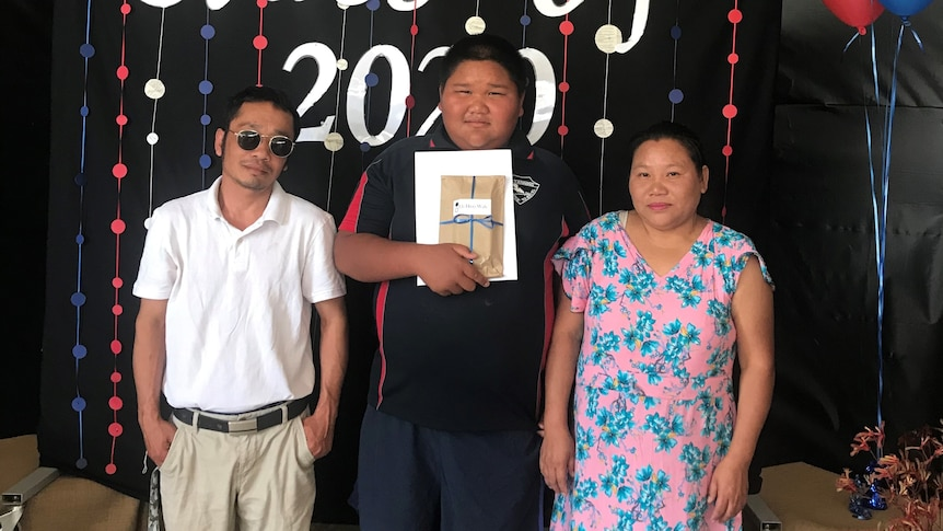 An Asian boy stands proudly between his parents.