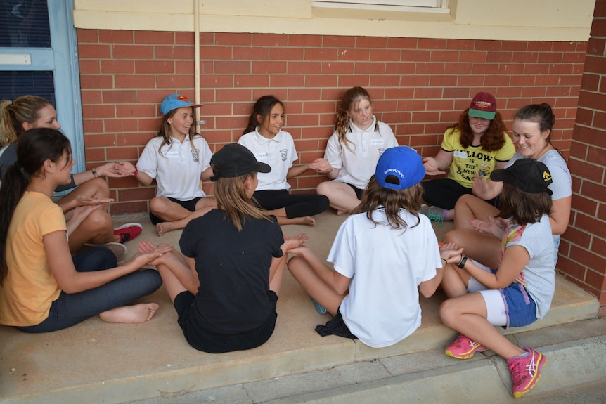 Eight students and two mentors sit in a circle with legs crossed, holding hands