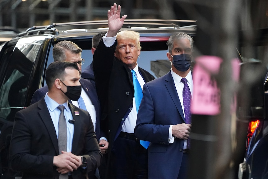 Donald Trump standing in the street near a car waves while surrounded by men in suits with surgical masks on.