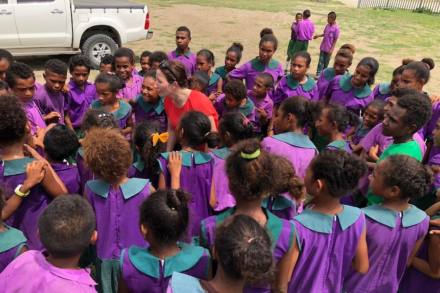 Mrs McDonald is surrounded by school children in PNG.