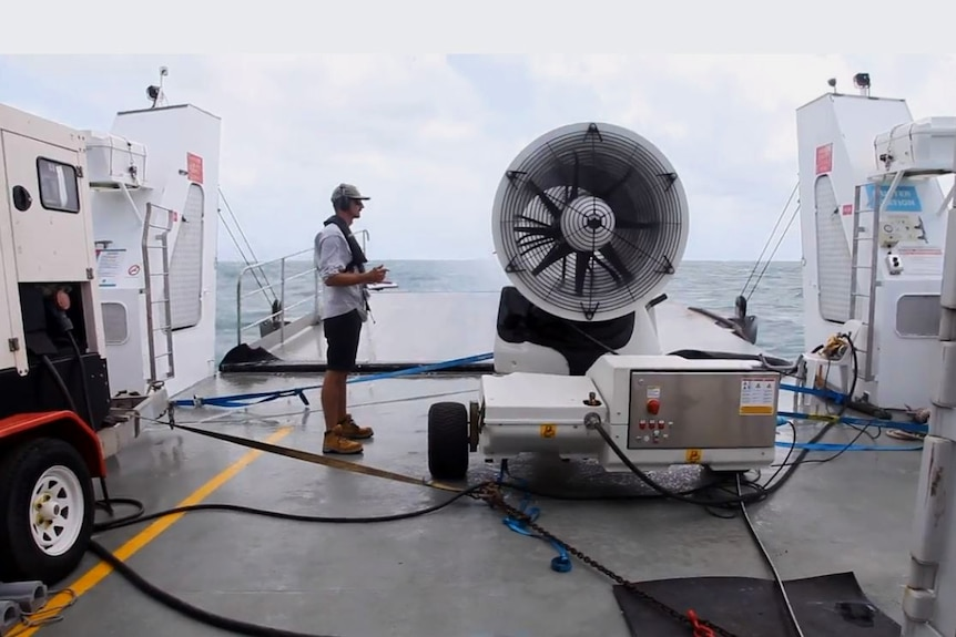 A man on a boat standing next to a big fan taking notes