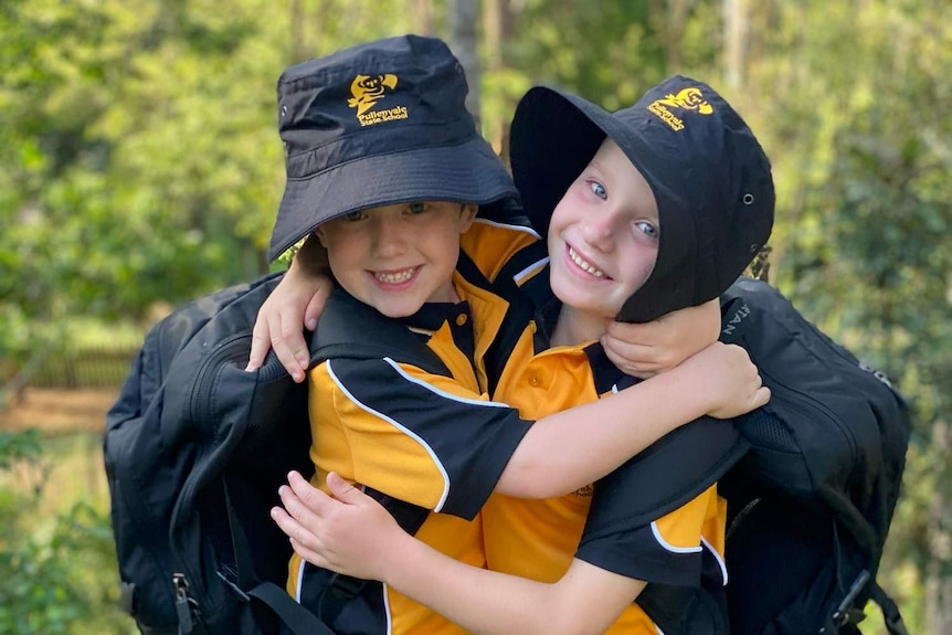 Twins Nixon and Mitchell Conradi hug each other with their backpacks and hats on.