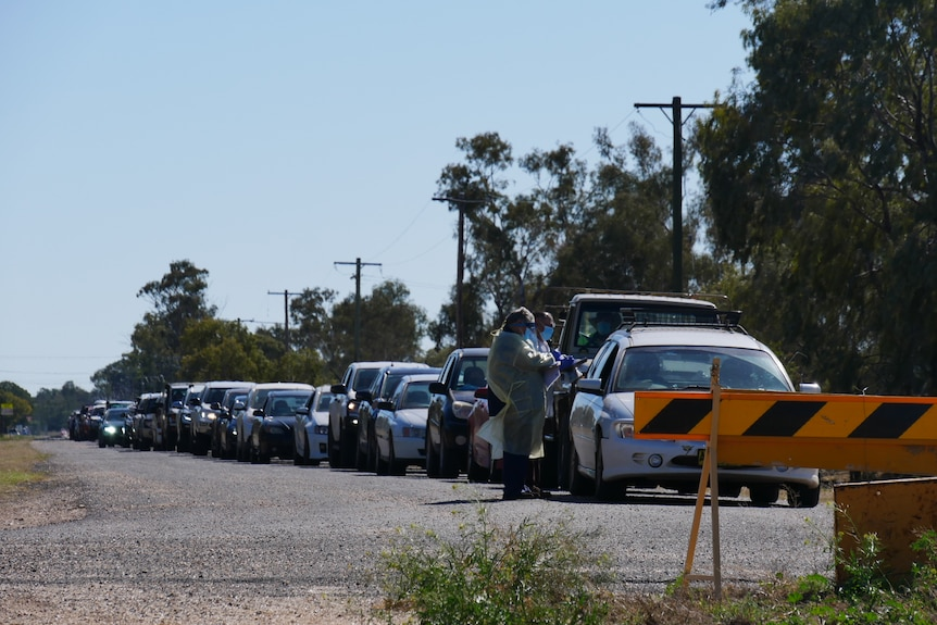 A queue of cars with healthcare professionals in covid protective gear in front of the queue